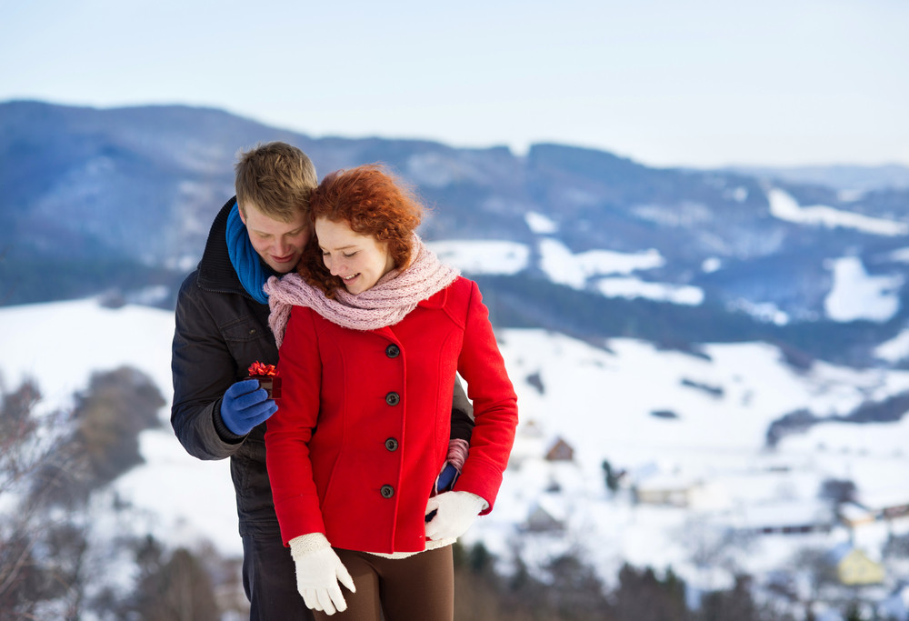 A young man is asking to married a beautiful girl in snow country.