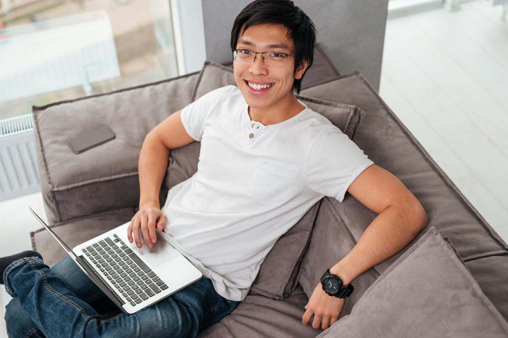 Above portrait of asian man with laptop on sofa. looking at camera