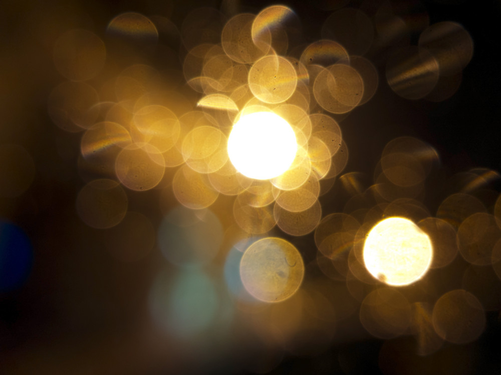 abstract black background, gold bubble lights or snowflakes falling at night. Bokeh Christmas background with circle designs or blurred stars shining, glitter magic background