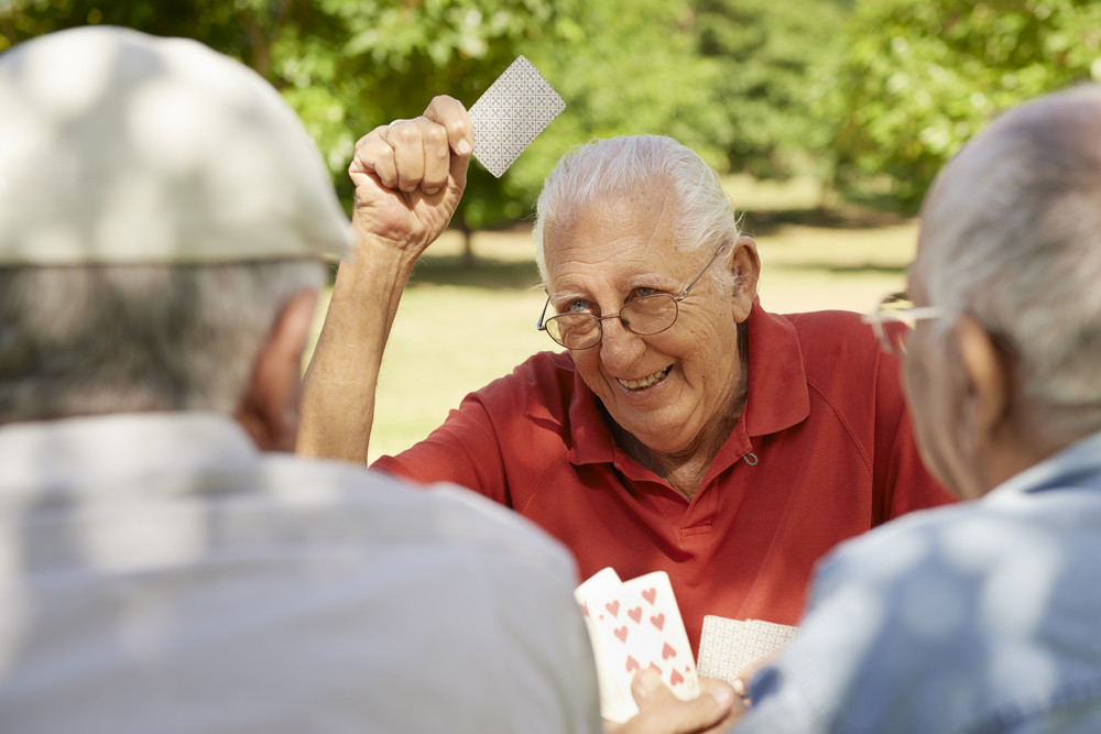 Active retirement, old people and seniors free time, group of three elderly men having fun and playing cards game at park