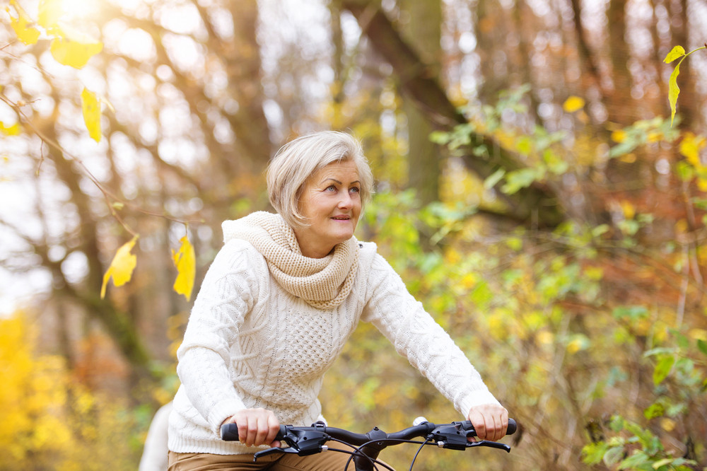 Active senior woman riding bike in autumn nature. They having romantic time outdoor.