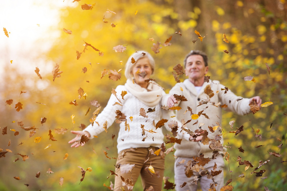 Active seniors having fun and playing with the leaves in autumn forest