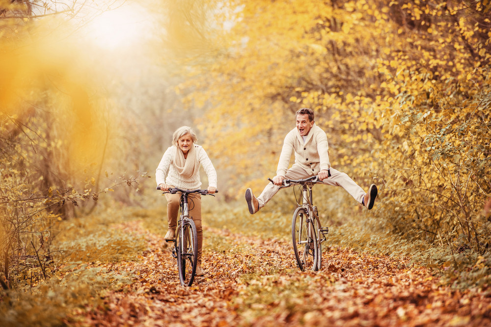 Active seniors riding bike in autumn nature. They having fun outdoor.