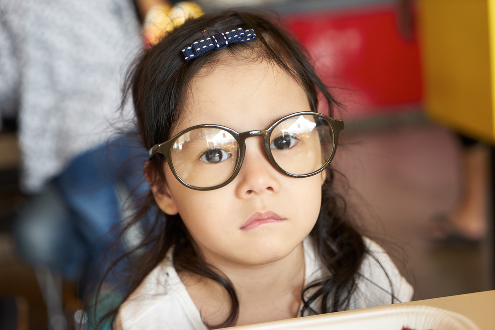 Adorable serious little girl and big funny glasses on her face. Toned image with shallow depth of field