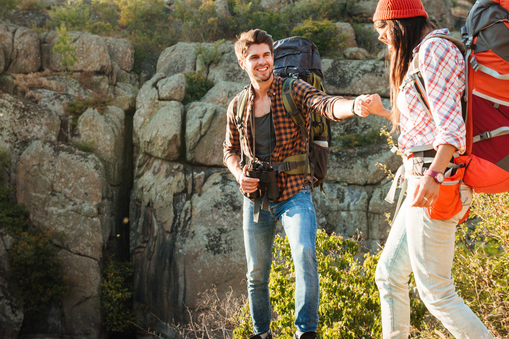 Adventure couple walking on rocks near the canyon