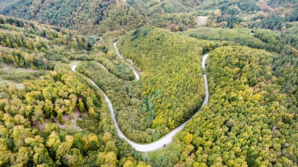 Aerial view of curvy road in the middle of green forest, low hills. Nova Bana, Slovakia.