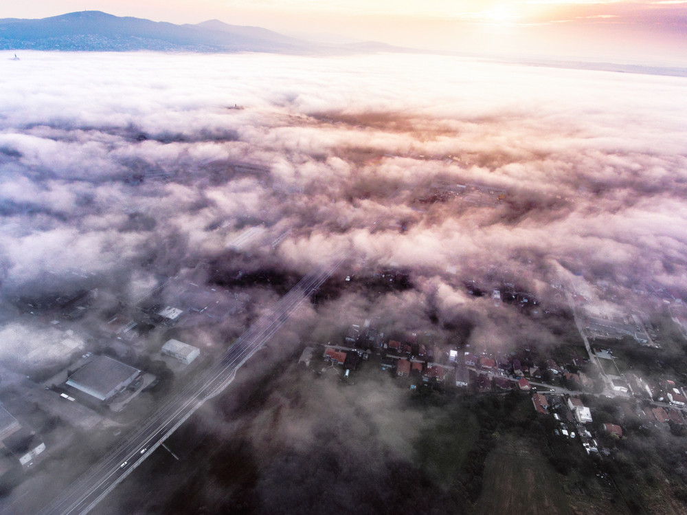 Aerial view of highway, mornig town covered by mist. Hills. Sun rising. Netherlands