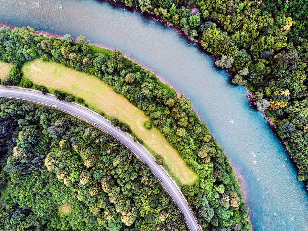 Aerial view of highway, river, forest and grassland during summer day. Slovakia.