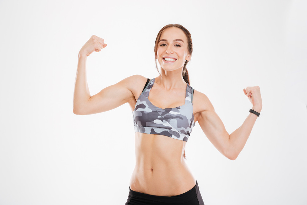 Aerobic woman showing biceps. looking at camera. isolated white background