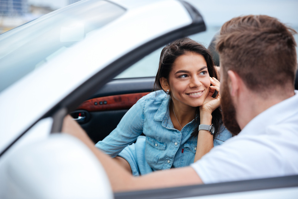 Affectionate young couple on vacation travelling by their car