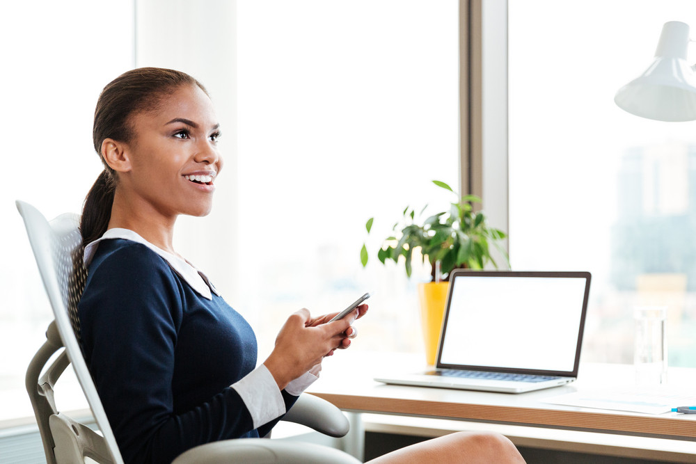 African business lady in dress sitting by the table and holding phone in office. Side view