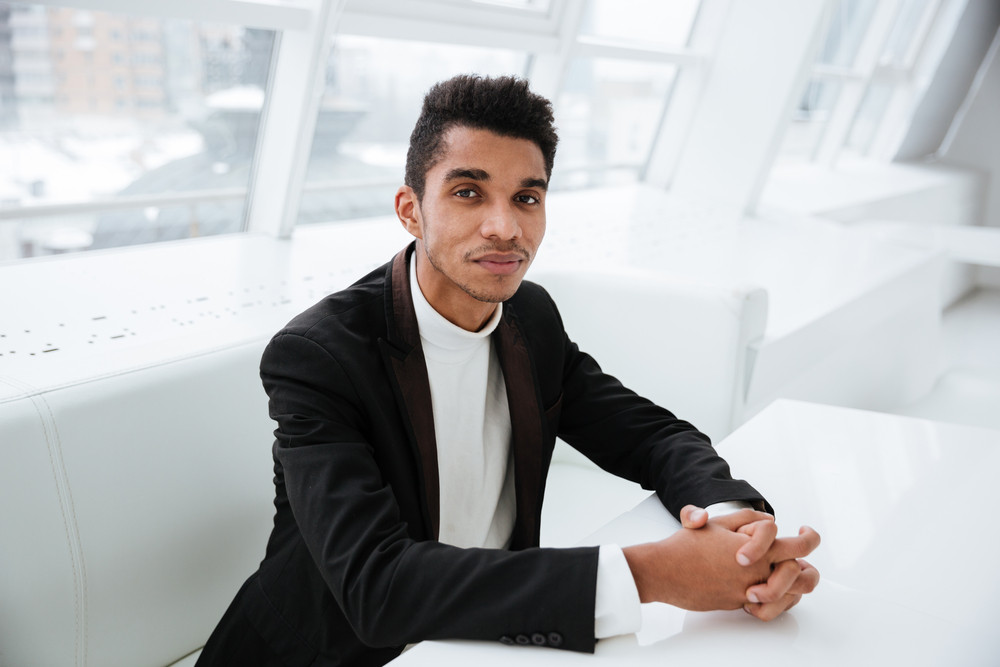 African business man in black suit sitting at the table in office and looking at camera
