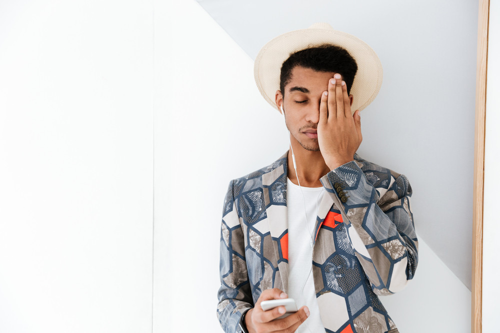 African business man in unusual suit and hat covering one eye of his hand and holding phone