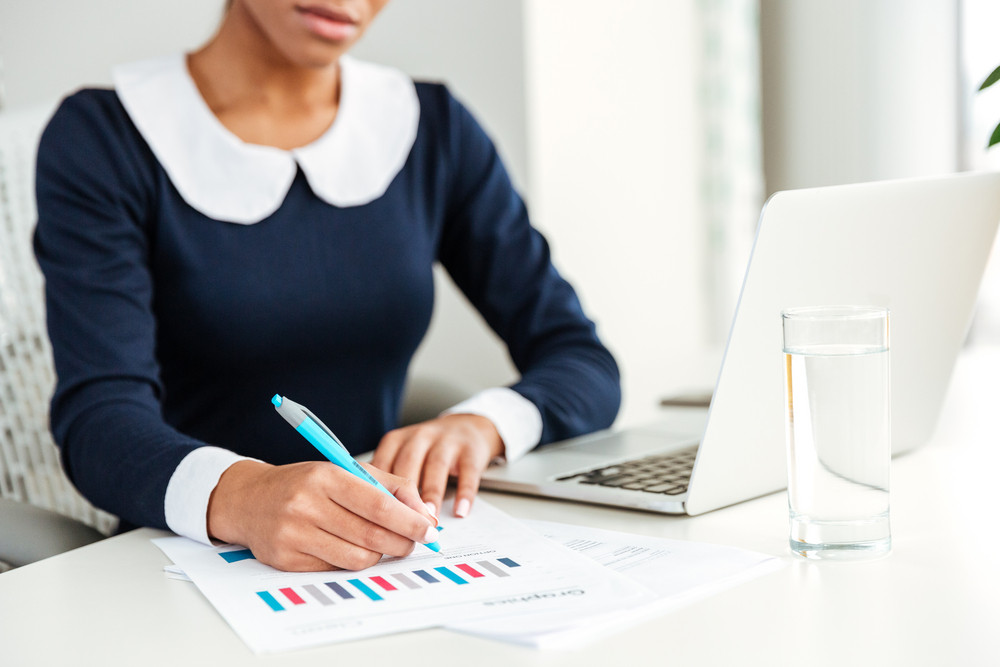 African business woman in dress sitting by the table and writing something on workplace. Cropped image