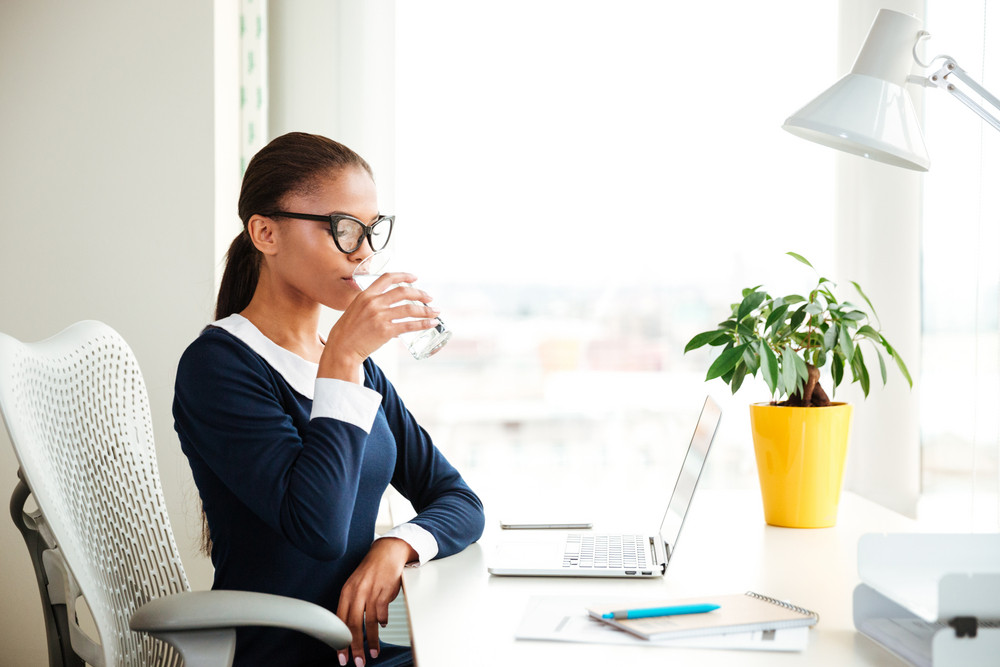 African business woman in dress sitting on armchair and drinking water in office