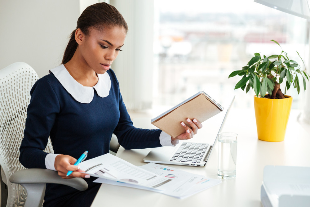 African business woman in dress working with laptop and documents on workplace near the window
