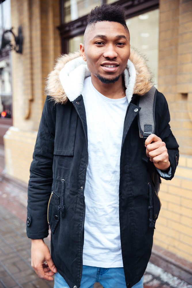 African handsome man walking on the street. Looking at camera.