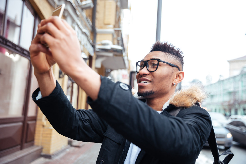 African happy man holding his cellphone in hands and make a selfie outdoors.
