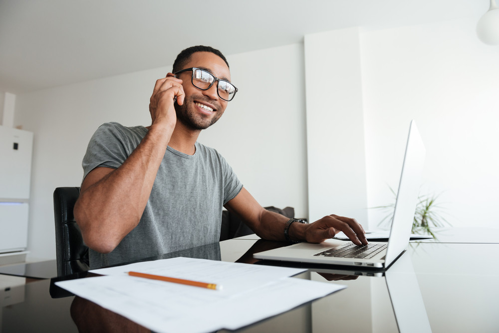 African man dressed in grey t-shirt and wearing eyeglasses talking on cellphone while using laptop.