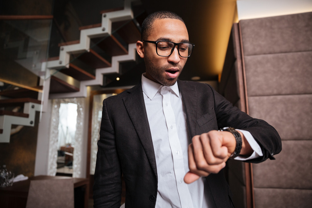 African man in glasses and suit looking at wristwatch in hotel