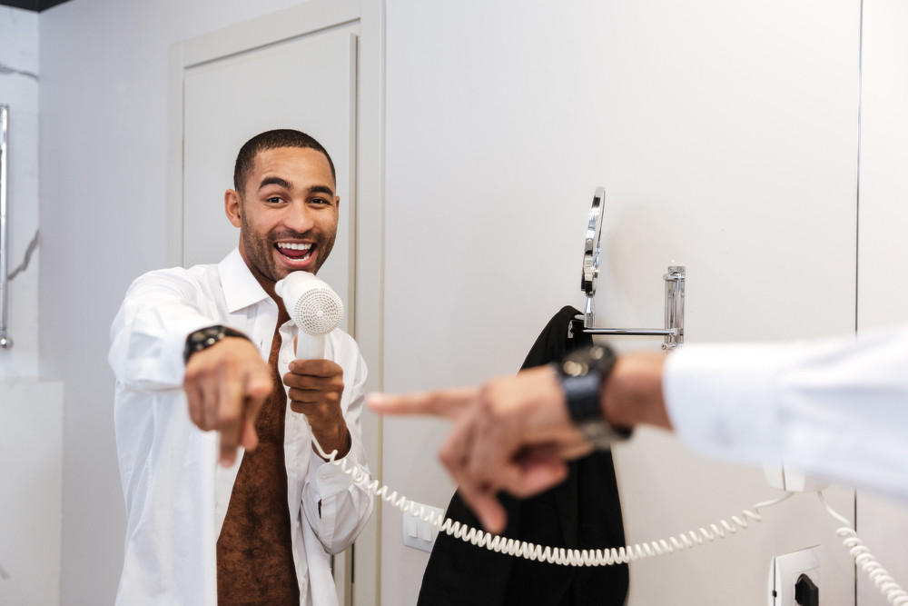 African man in shirt sings with hairdryer in hand and pointing at mirror in bathroom