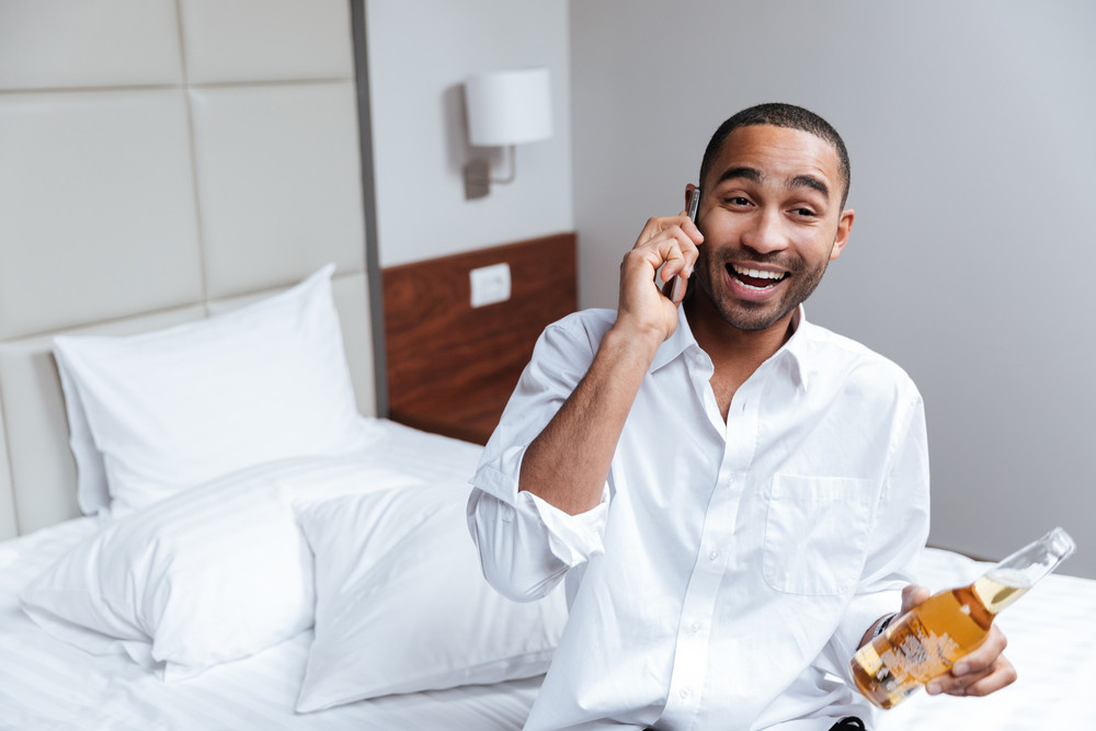 African man in shirt talking at phone on bed with beer in hand in hotel room
