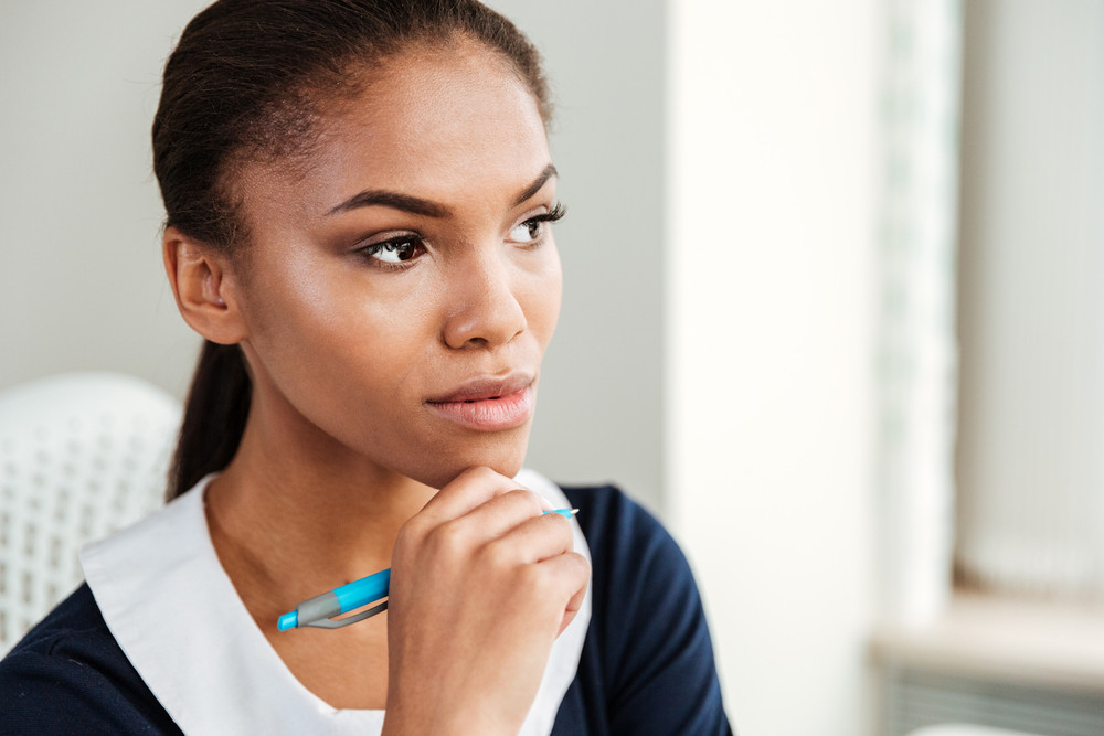 African pensive business woman in dress standing in office and holding hand ner the face