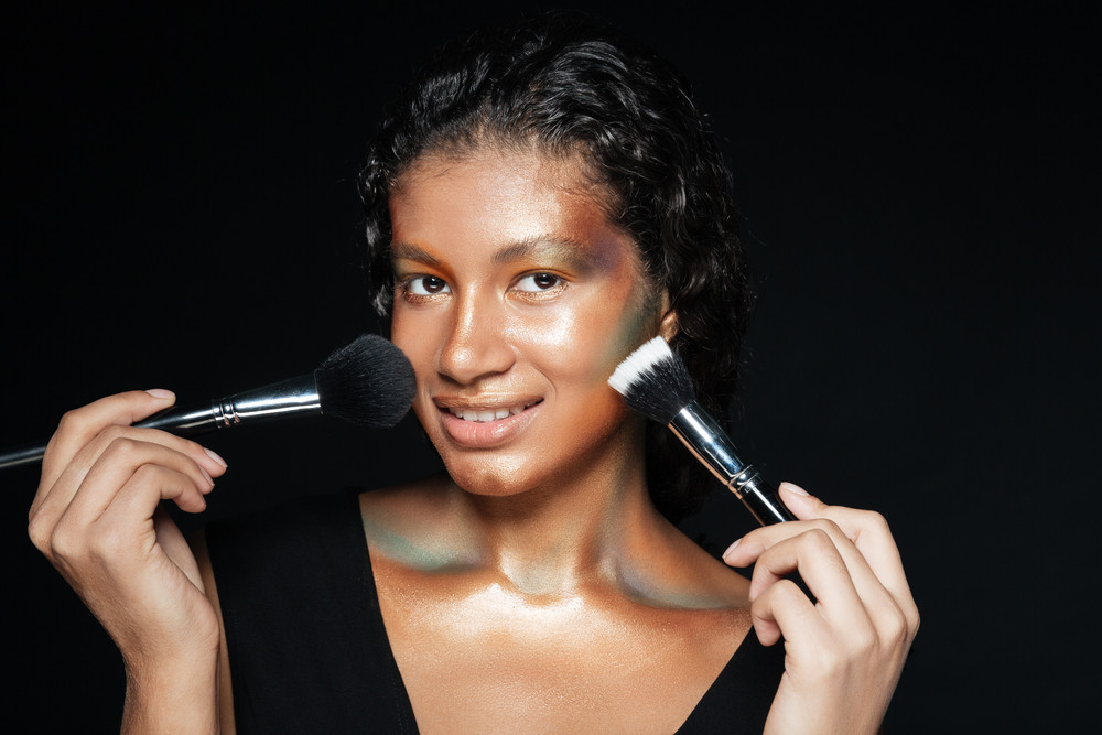 African woman with brush in studio. looking at camera. isolated black background