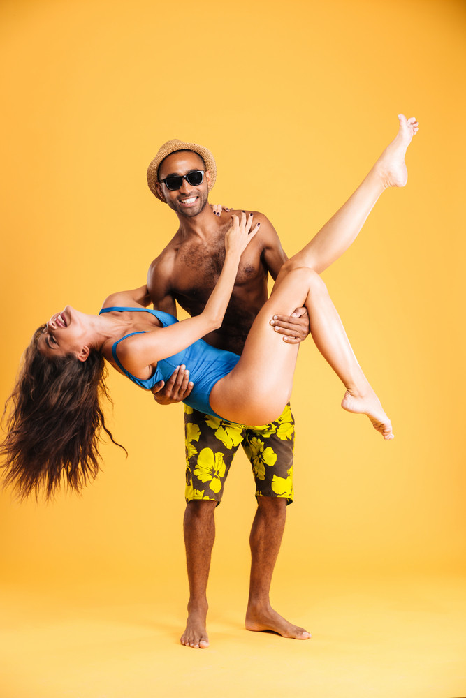 Afro american man holding his girlfriend with two hands isolated on orange background