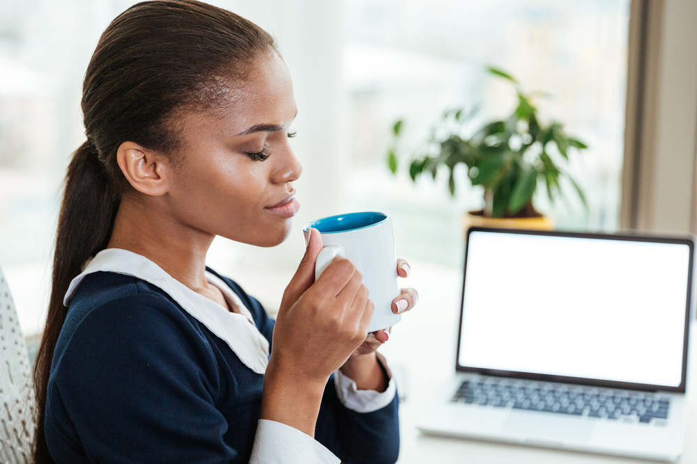 Afro Business woman in blue dress sitting by the table with tea in office. Side view