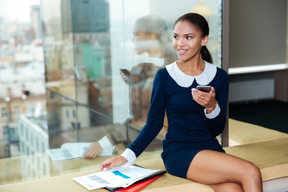 Afro Business woman in dress sitting near the window with phone and folder and looking aside in office