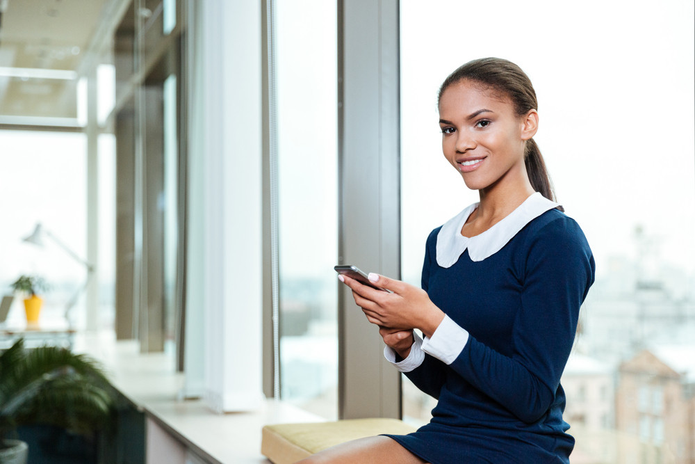 Afro Business woman in dress sitting near the window with phone in office and looking at camera