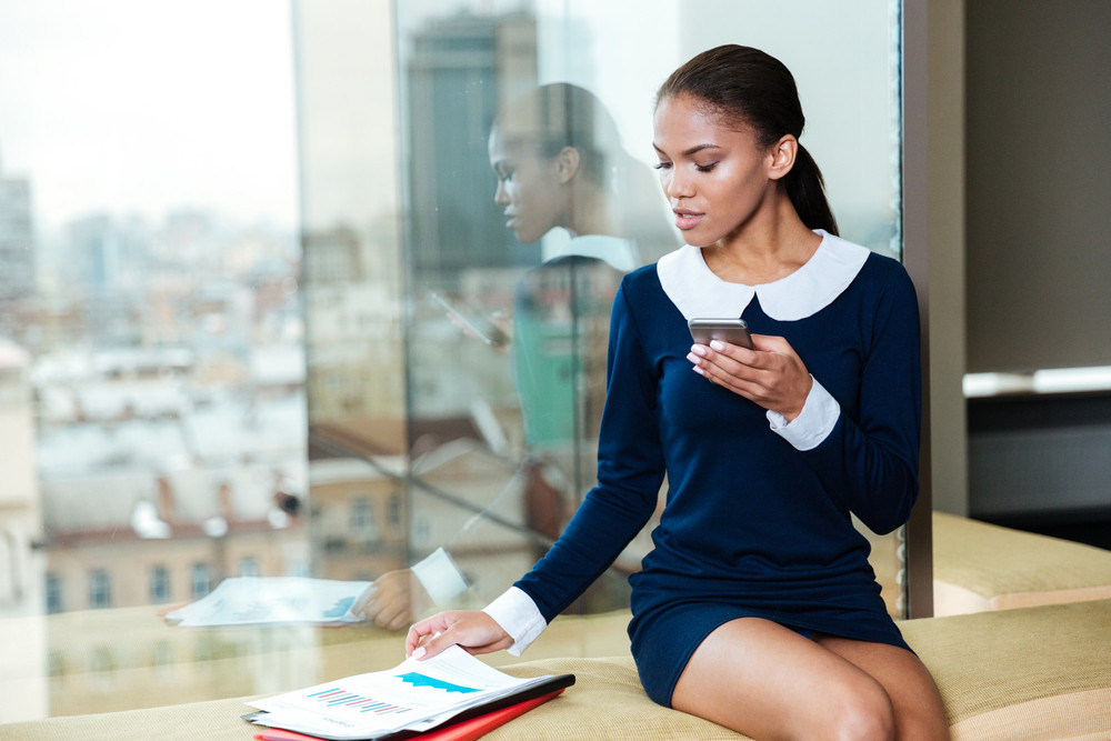 Afro Business woman siiting near the window, holding phone in hands and looking at documents