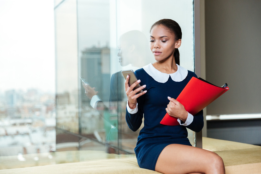Afro business woman sitting near the window with folder in hand and looking at phone