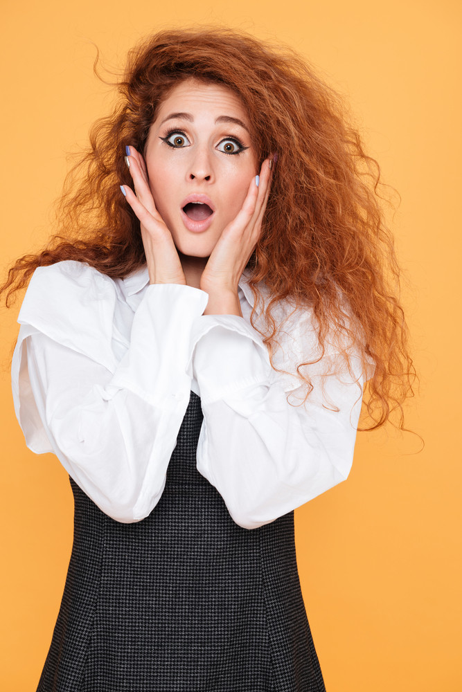 Amazed astonished young woman standing with mouth opened