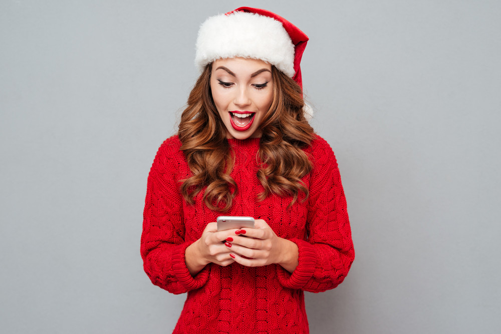 Amazed attractive young woman in santa claus hat using cell phone