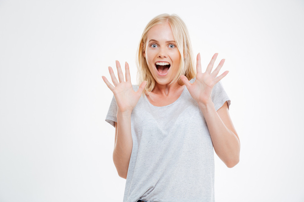 Amazed blonde woman looking at camera isolated on a white background