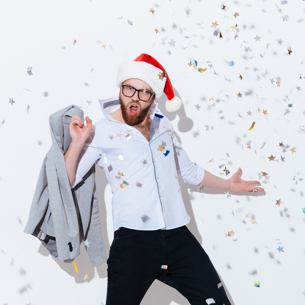 Amazed excited bearded man in santa claus hat standing and shouting over white background