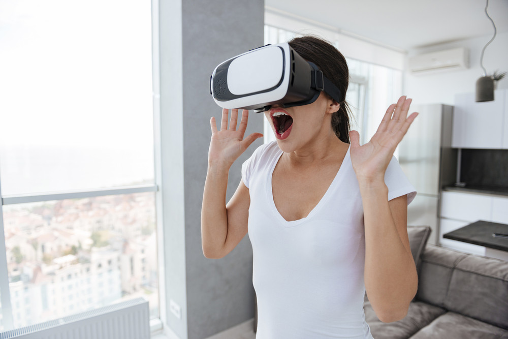 Amazed happy young woman with raised hands and opened mouth using virtual reality googles at home