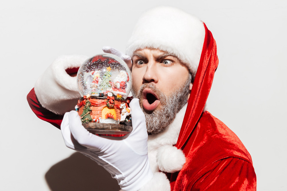 Amazed man santa claus holding and looking at snow globe