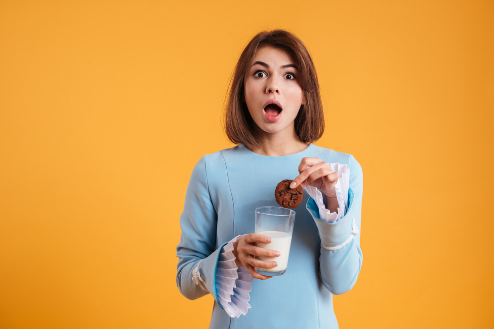 Amazed pretty young woman putting cookie into the glass with milk over yellow background