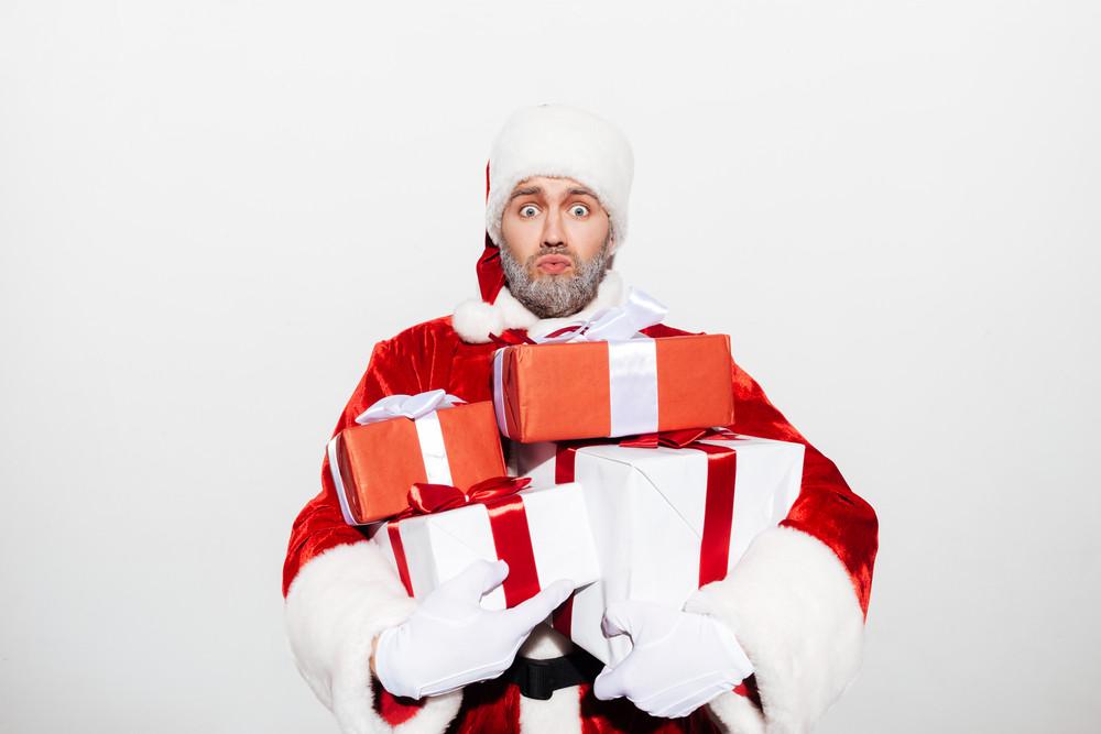 Amazed shocked man santa claus holding pile of gift boxes