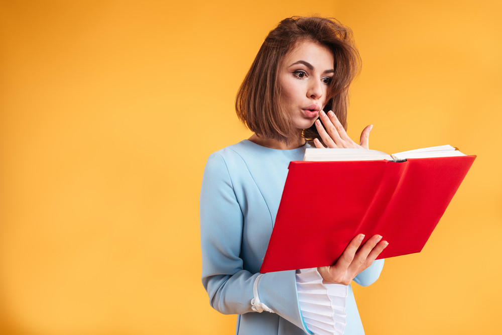 Amazed young woman holding and reading red book over yellow background