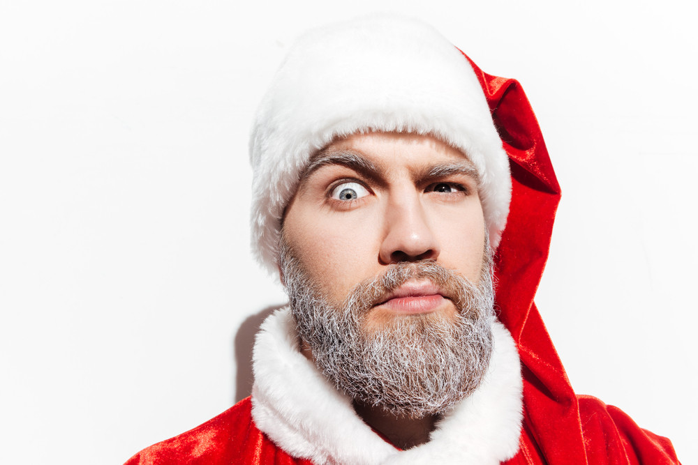 Amusing strict man in santa claus costume and hat