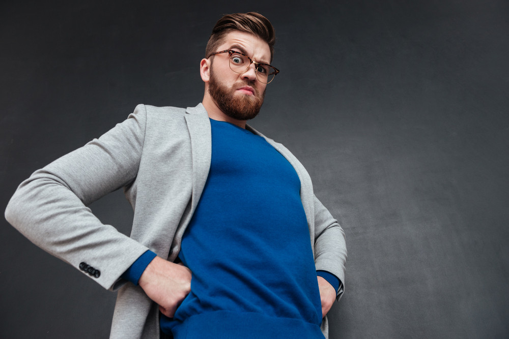 Angry bearded young businessman in glasses standing with hands on waist