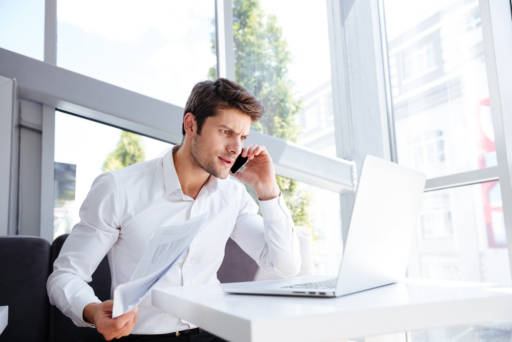 Angry irritated young businessman with laptop and documents talking on mobile phone in office
