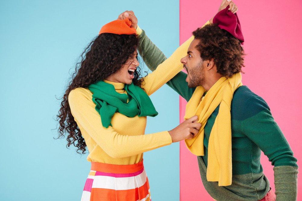 Angry irritated young couple in hats and scarves standing and arguing