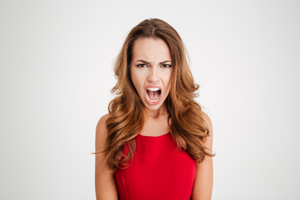 Angry irritated young woman standing and shouting over white background