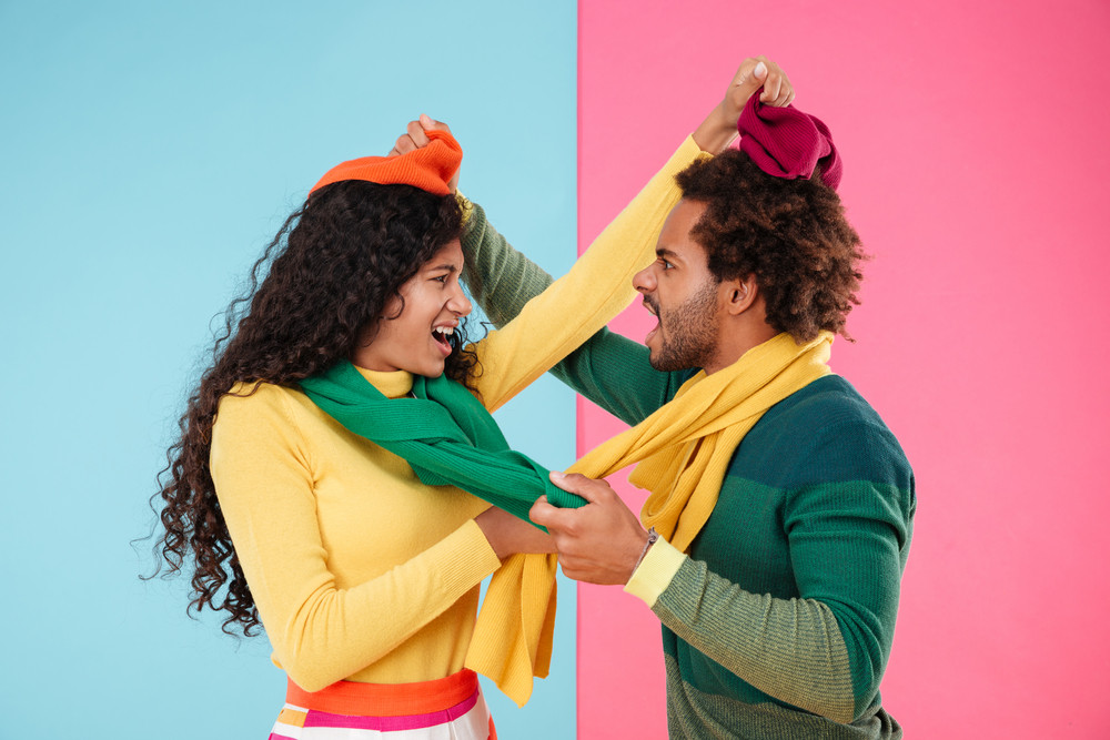 Angry mad african couple in hats and scarves standing and arguing over colorful background