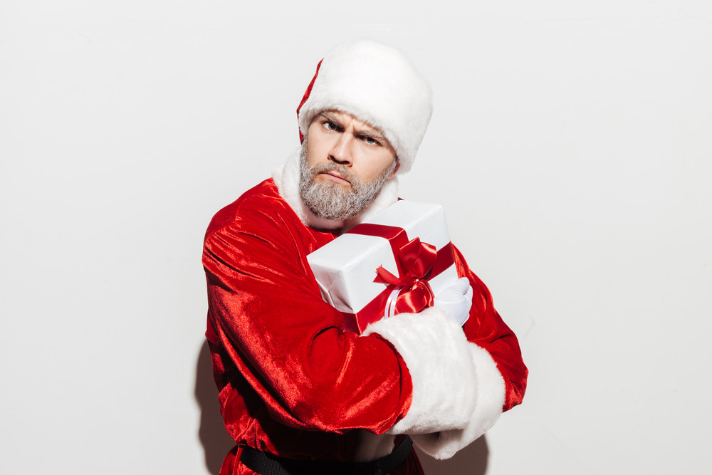 Angry man santa claus standing and holding present box